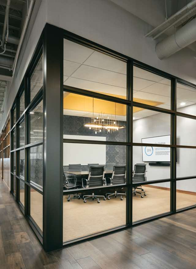 A conference room surrounded by clear, glass windows in a hallway at Life Time Work