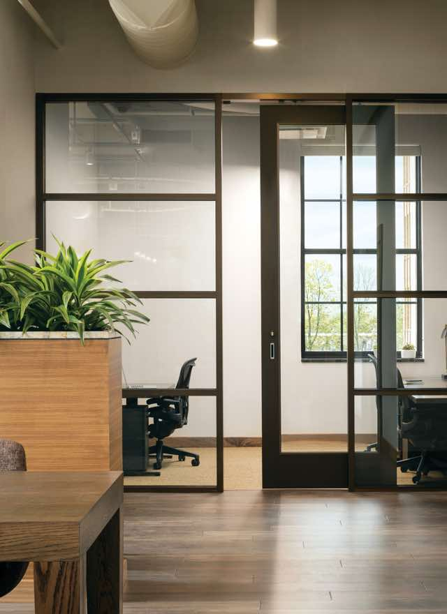 Two offices with clear glass doors and windows in a workspace with shiny wooden floors