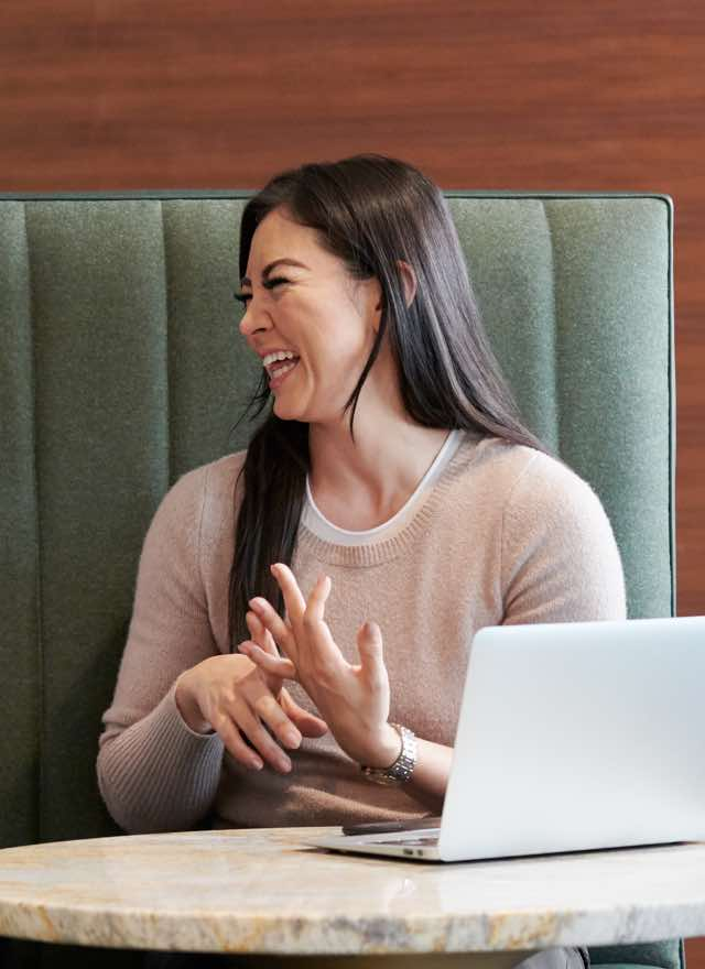 Two women sitting next to each other smiling and laughing in an office setting