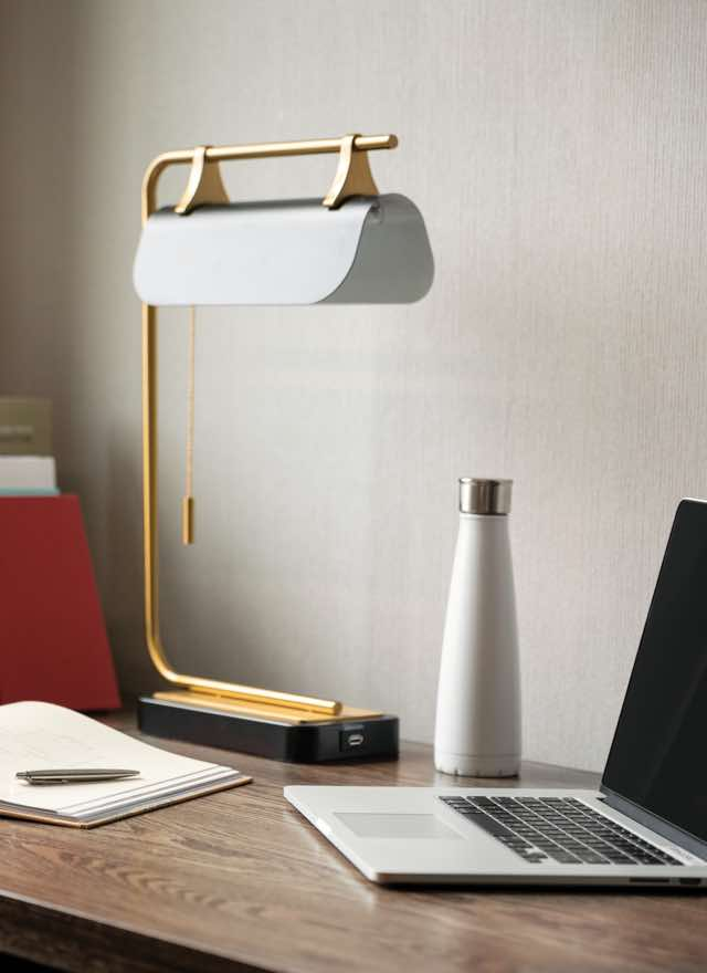 A laptop, lamp, notebook and water bottle on a large wooden desk