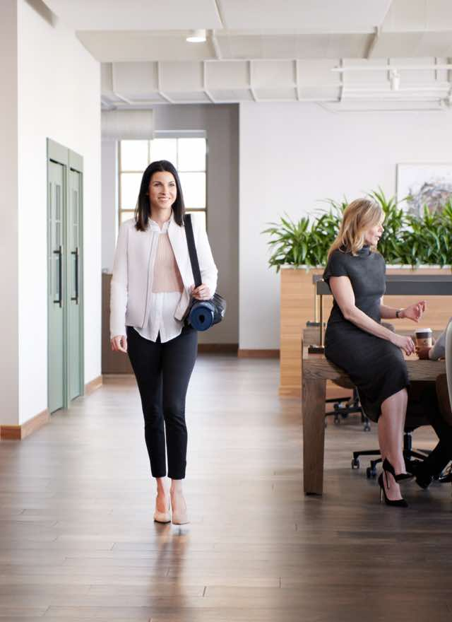 Woman walking through an office setting at Life Time Work